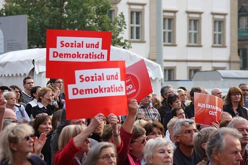 """Blick auf Zuhörerinnen und Zuhörer während der Rede von Franz Müntefering, die Schilder mit der Aufschrift """"Sozial und Demokratisch"""" in die Höhe halten"""