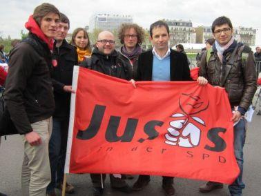 Gruppenbild der Jusos Erlangen mit Benoît Hamon hinter einer Juso-Fahne