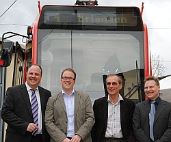 """Die Fraktionsvorsitzenden vor einer Straßenbahn mit der Aufschrift """"Erlangen"""""""