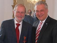 Robert Thaler mit dem Verdienstkreuz, daneben Staatsminister Joachim Herrmann