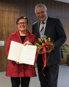 Gisela Niclas mit der Urkunde zum Bundesverdienstkreuz, daneben Innenminister Joachim Herrmann