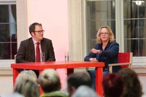 Florian Janik und Natascha Kohnen sitzen gemeinsam an einem roten Tisch auf der Bühne und sprechen miteinander